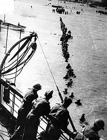 Men wading out from the beach to a rescue ship May 1940